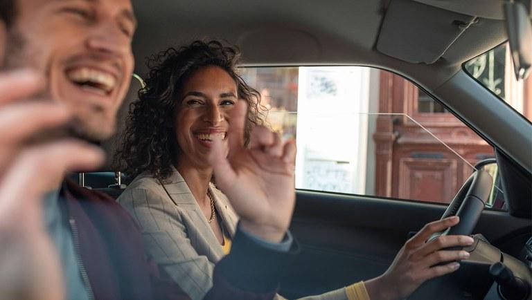 Ein Mann und eine Frau in einem Hybrid Modell von Suzuki, sie fährt, beide lachen.