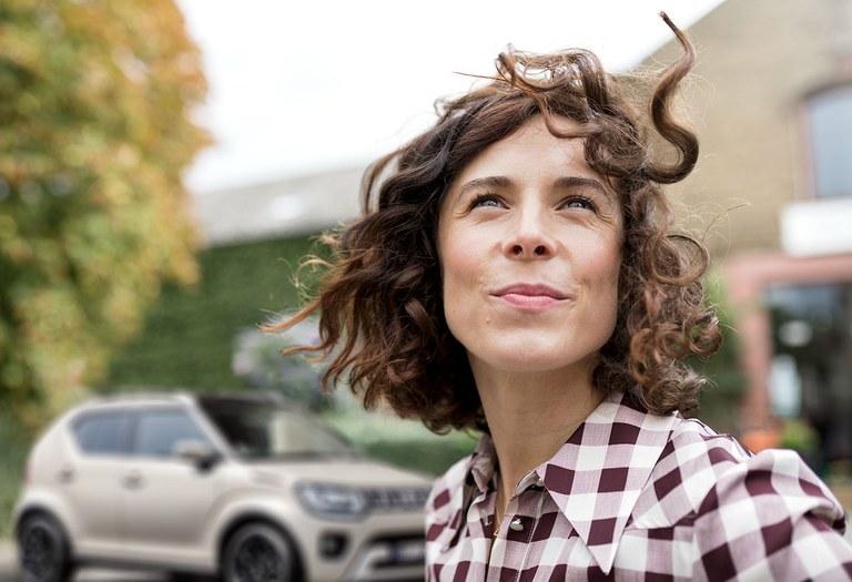 Frau schaut in den Himmel, im Hintergrund ein verschwommener Suzuki Ignis Hybrid in Pure White Pearl Metallic.