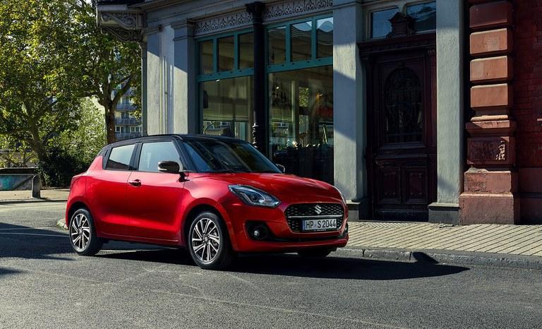 Suzuki Swift Hybrid in Burning Red Pearl Metallic parkt vor einem Gebäude an der Straßenecke.