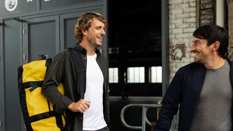 Zwei Männer laufen von links nach rechts, vor einer Halle. Der hintere trägt eine gelbe Tasche.