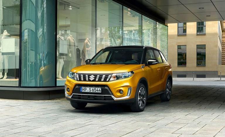 Suzuki Vitara Hybrid in Solar Yellow Pearl Metallic steht vor einem Modegeschäft.