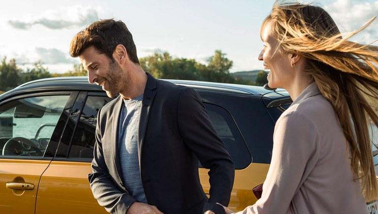 Eine Frau und ein Mann laufen von rechts nach links, vor einem Suzuki Vitara Hybrid in Solar Yellow Pearl Metallic.