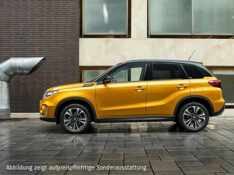 Seitliche Aufnahme eines Suzuki Vitara Hybrid in Solar Yellow Pearl Metallic, auf einer nassen Straße stehend.