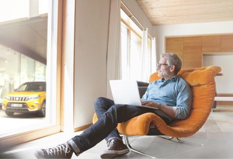 Mann sitzt zu Hause auf einem Sessel und hat seinen Laptop auf dem Schoß.