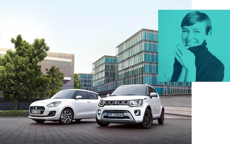 Ein Suzuki Swift Hybrid und ein Suzuki Ignis Hybrid  in Pure White Pearl Metallic, stehen vor einem Bürogebäude.