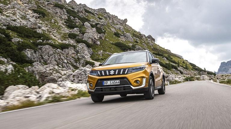 Von vorn fotografierter Suzuki Vitara Hybrid in Kinetic Yellow, auf einem Geröllweg.