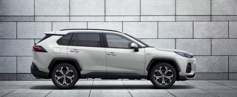 Seitlich fotografierter Suzuki Across Hybrid in White Pearl Crystal Shine Metallic, Fokus auf dem Privacy Glass der hinteren Fenster.