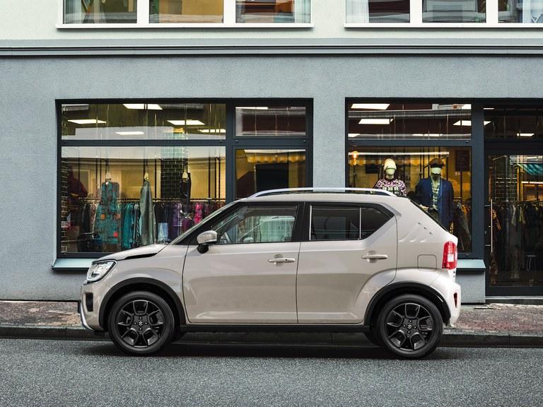 Von der Seite fotografierter Suzuki Ignis Hybrid in Caravan Ivory Pearl Metallic, vor einem Geschäft geparkt.