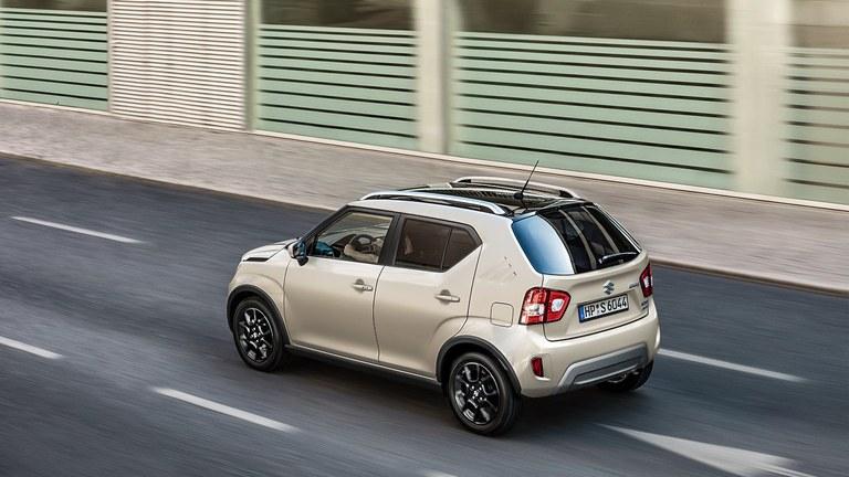 Seitlich von hinten fotografierter Suzuki Ignis Hybrid in Caravan Ivory Pearl Metallic, auf einer Straße fahrend.