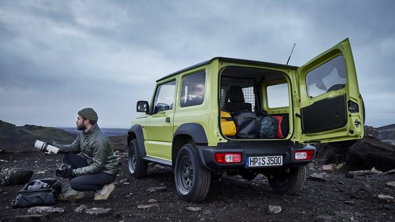 Suzuki Jimny Hybrid in Kinetic Yellow mit geöffnetem Gepäckraum, daneben ist ein Mann in der Hocke und schaut in die Ferne