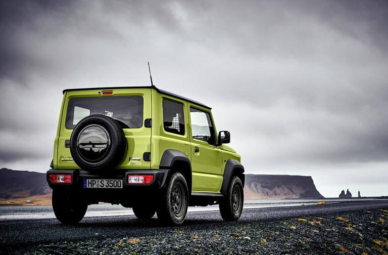 Seitlich von hinten fotografierter Suzuki Jimny Hybrid in Kinetic Yellow, Fokus auf der Heckpartie.