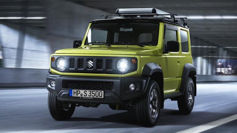Suzuki Jimny Hybrif in Kinetic Yellow fährt mit eingeschalteten LED-Scheinwerfern duch einen Tunnel.