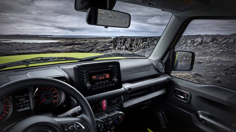 Aufnahme des Innnenraums eines Suzuki Jimny Hybrid in Kinetic Yellow, im Hintergrund eine Felsenlandschaft.
