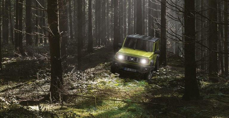 Suzuki Jimny Hybrid in Kinetic Yellow in einem nebeligen Wald, mit eingeschaltetem Licht.