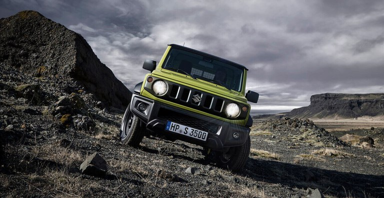 Suzuki Jimny Hybrid in Kinetic Yellow im Gelände - Licht an.