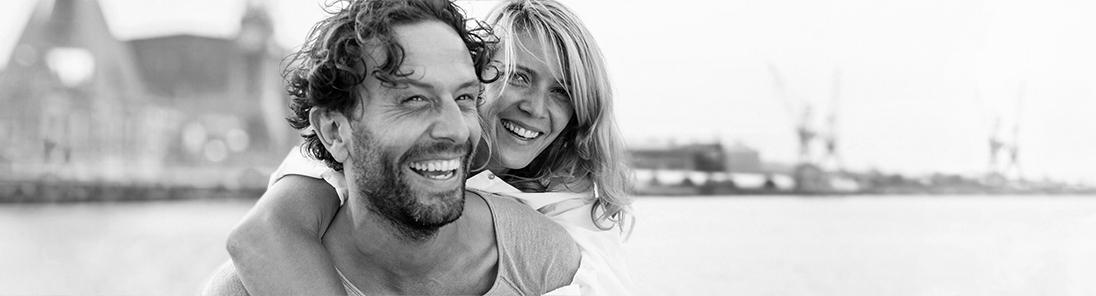 Lachendes Paar vor verschwommener Stadt-Silhouette.