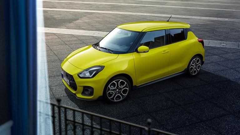 Schräg von der Seite fotografierter Suzuki Swift Sport Hybrid in Champion Yellow, aus einem Fenster herausfotografiert.