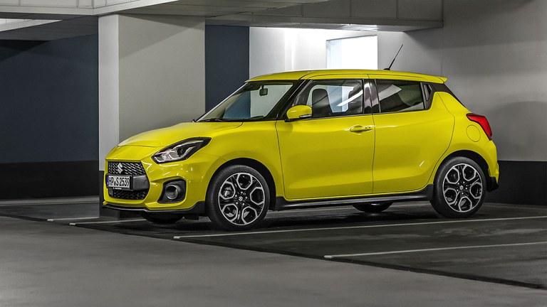 Ein leicht seitlich fotografierter Suzuki Swift Sport Hybrid in Champion Yellow in einer Parkgarage stehend.