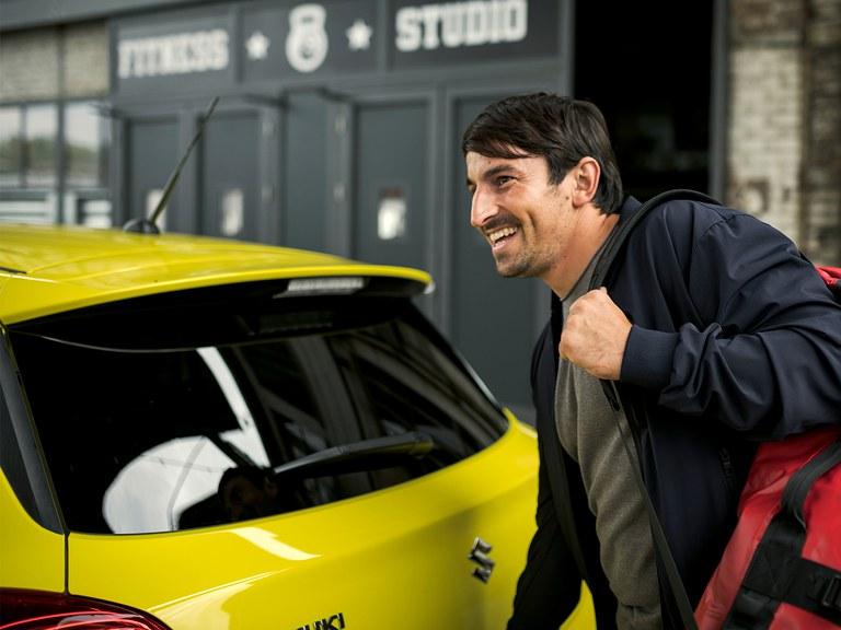 Mann mit Rucksack öffnet den Gepäckraum Suzuki Swift Sport Hybrid in Champion Yellow.