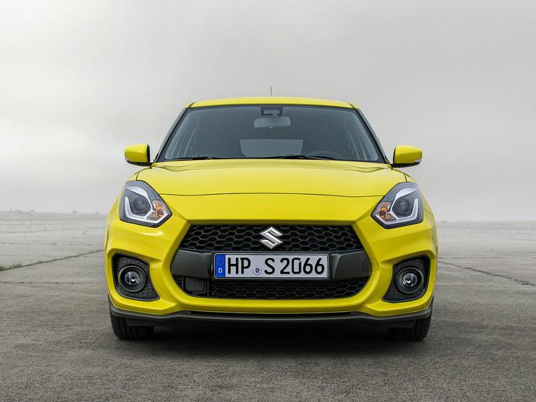 Von vorne fotografierter Suzuki Swift Sport Hybrid in Champion Yellow, Fokus auf der Frontpartie.