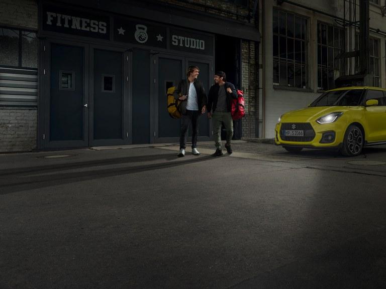 Zwei Männer verlassen ein Fitness Studio, daneben steht ein Suzuki Swift Sport Hybrid in Champion Yellow mit Guide me Light.