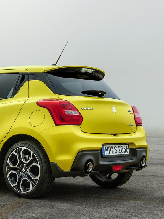 Von hinten fotografierter Suzuki Swift Sport Hybrid in Champion Yellow, Fokus auf der Heckpartie.