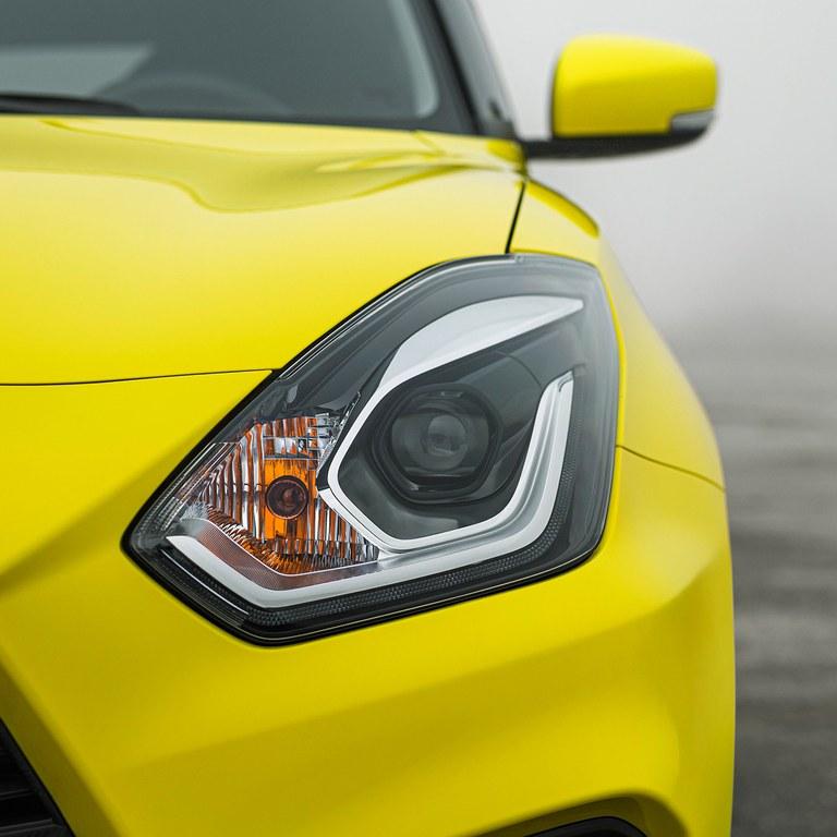 Detailaufnahme des linken Frontlichts eines Suzuki Swift Sport Hybrid in Champion Yellow