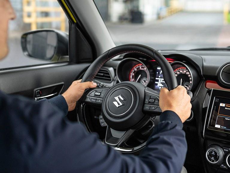Aufnahme des Lenkrads eines Suzuki Swift Sport, man sieht verschwommen zwei Hände, welche das Lenkrad halten.