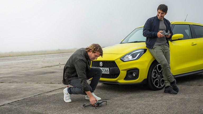 Suzuki Swift Sport Hybrid in Champion Yellow, davor zwei Männer, einer hält eine kleine Drone, der andere die Fernbedienung.