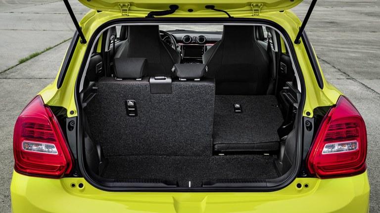 Suzuki Swift SportVon hinten fotografierter Suzuki Swift Sport Hybrid in Champion Yellow, Fokus auf dem offenen Gepäckraum. Gepäckraum