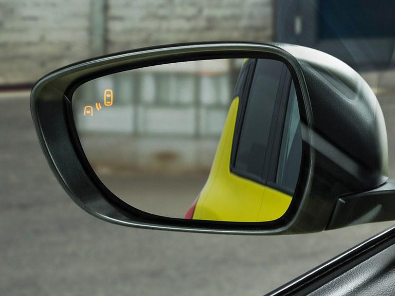 Detailaufnahme des linken Außenspiegels mit Totem-Winkel-Warnsystem eines Suzuki Swift Sport Hybrid.