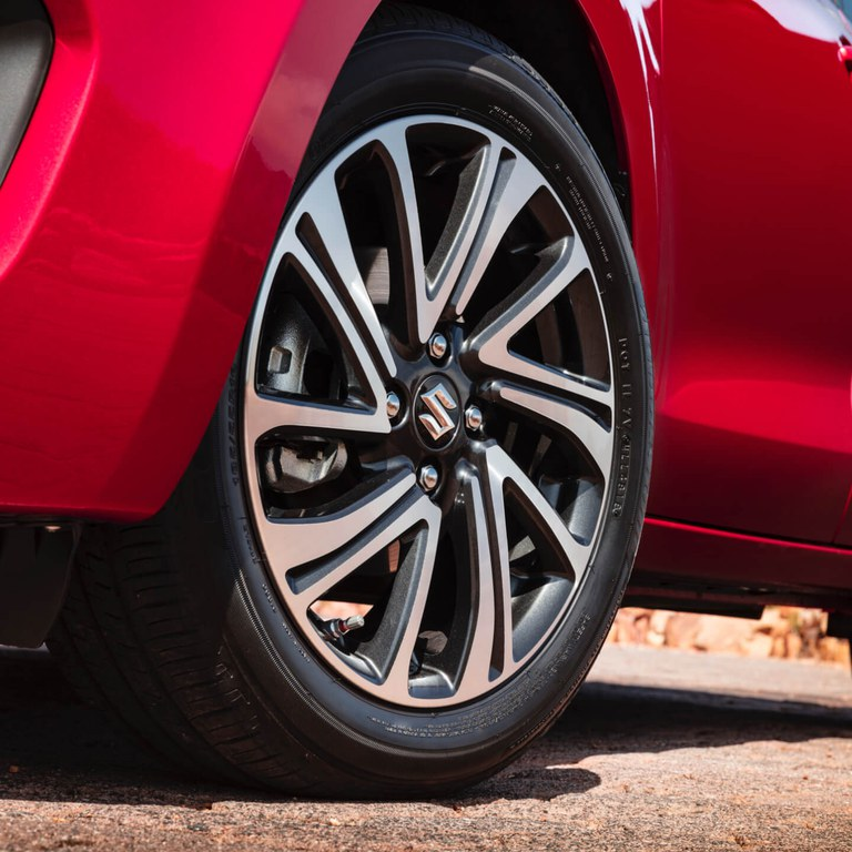 Detailaufnahme der Alufelgen eines Suzuki Swift Hybrid in Burning Red Pearl Metallic.