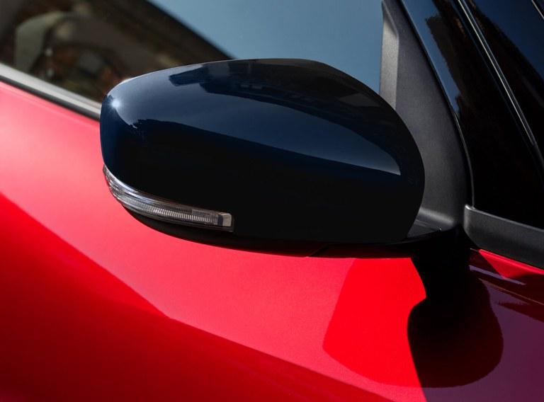 Detailaufnahme des Außenspiegels eines Suzuki Swift Hybrid in Burning Red Pearl Metallic.