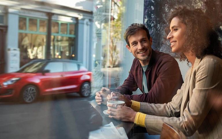 Mann und Frau sitzen in einem Café und schauen raus auf einen Suzuki Swift in Red Pearl Metallic.