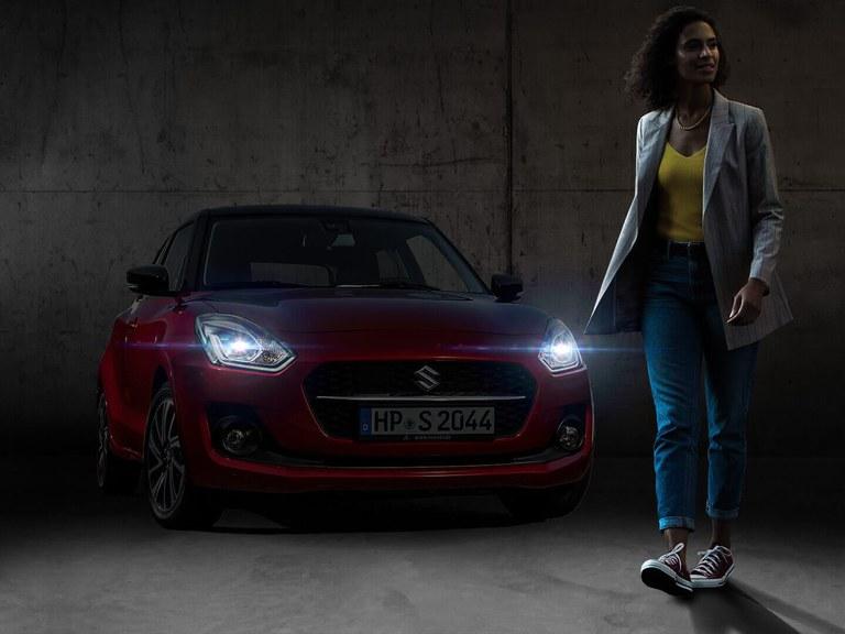 Eine Frau entfernt sich von einem geparkten Suzuki Swift Hybrid in Red Pearl Metallic mit eingeschaltetem Guide me Light.