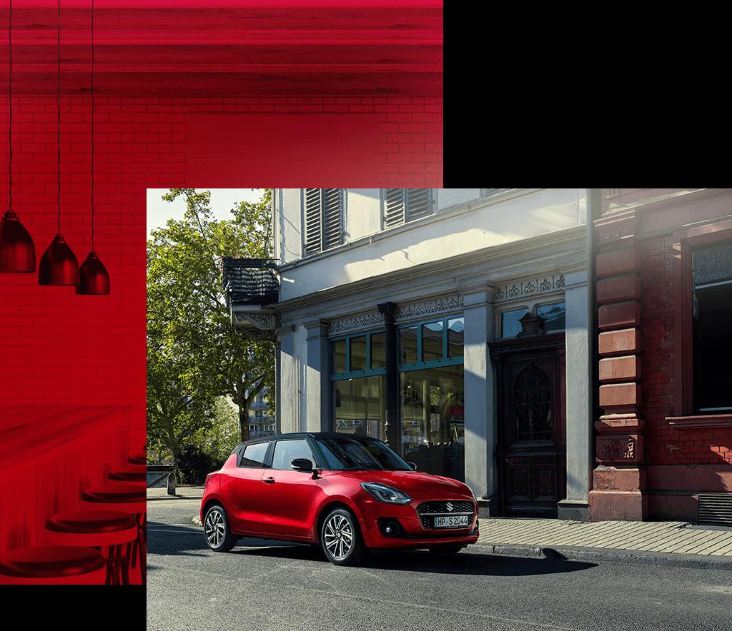 Suzuki Swift Hybrid in Burning Red Pearl Metallic steht vor einem Gebäude.