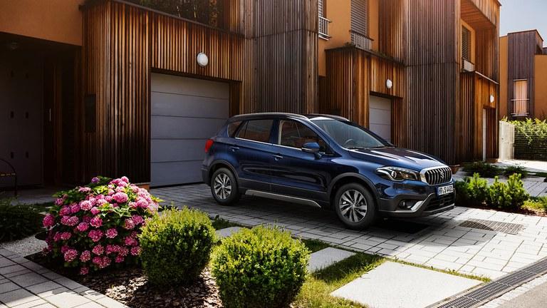 Suzuki SX4 S-Cross Hybrid in Blue Pearl Metallic steht vor einer Garage.