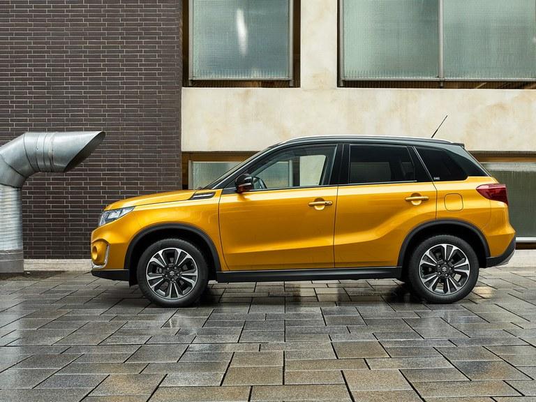 Suzuki Vitara Hybrid in Solar Yellow Pearl Metallic steht vor einem Gebäude auf verregnetem Boden.
