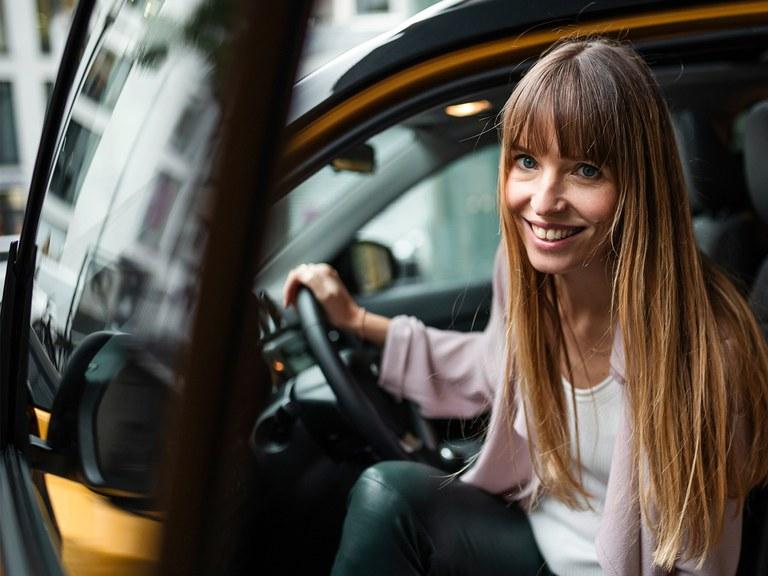 Frau mit langen braunen Haaren steigt aus dem Suzuki Vitara Hybrid in Solar Yellow Pearl Metallic und grinst in die Kamera.