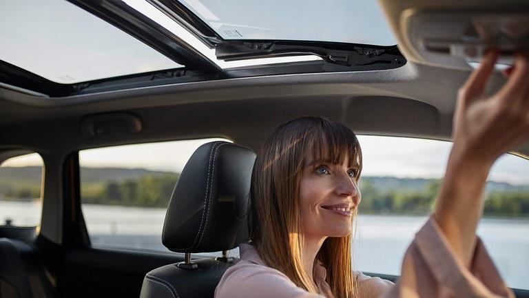 Frau mit langen braunen Haaren nun die Funktion des Panorama-Glasschiebehubdachs im Suzuki Vitara Hybrid.