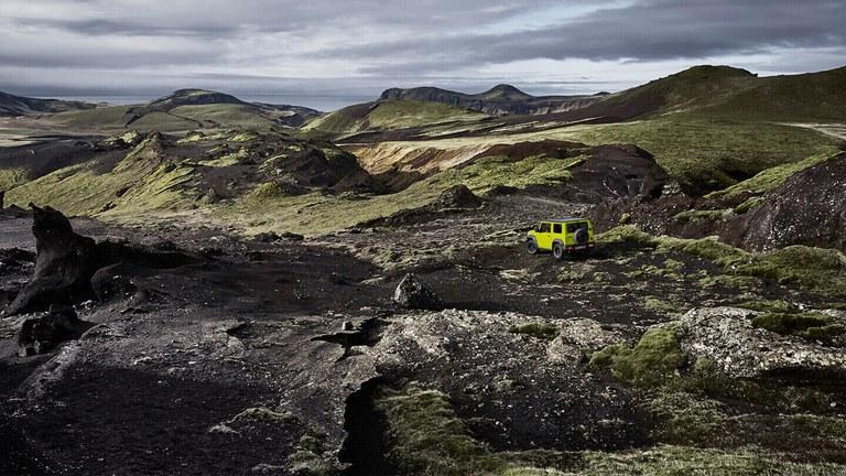 Suzuku Jimny Hybrid in Kinetic Yellow fährt durchs Gelände.