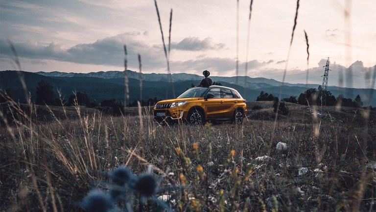 Ein seitlich fotografierter Suzuki Vitara Hybrid in Solar Yellow Pearl Metallic auf einem Weg in einem Tagbauwerk.