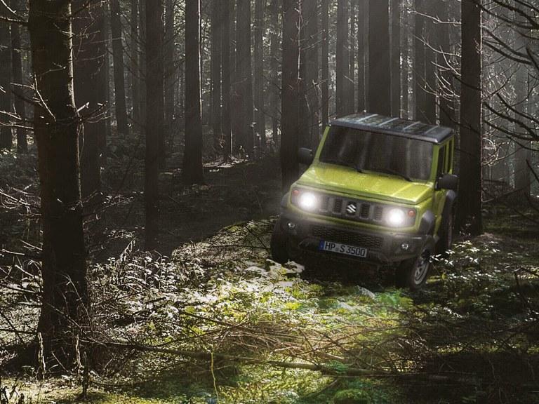 Suzuku Jimny Hybrid in Kinetic Yellow fährt durch den Wald.