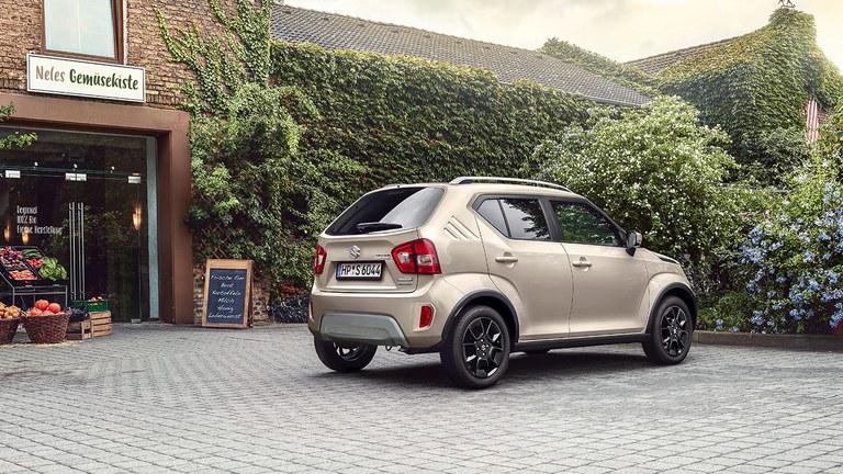 Seitlich von vorne fotografierter Suzuki Ignis Hybrid in Caravan Ivory Pearl Metallic, vor einem Hofladen geparkt.