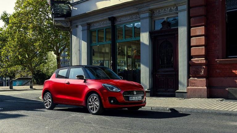 Schräg von der Seite fotografierter Suzuki Swift Hybrid in Burning Red Pearl Metallic, vor einem Cafe geparkt.