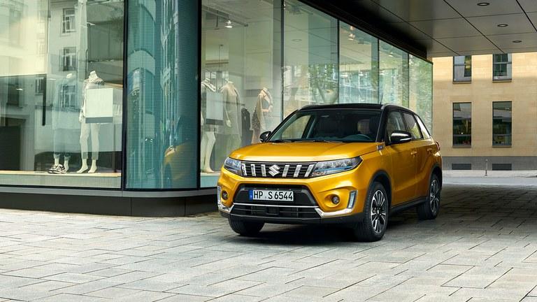 Leicht seitliche Aufnahme eines Suzuki Vitara Hybrid in Solar Yellow Pearl Metallic, neben einem Geschäft stehend.