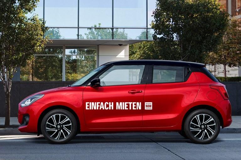 """Suzuki Swift Hybrid in Red Pearl Metallic mit der Aufschrift """"Einfach mieten - Suzuki NOW"""" steht am Straßenrand."""